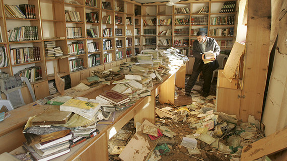 A Palestinian man inspects the damage to a library inside al-Eslah mosque after local witnesses said it was hit by an Israeli airstrike in Gaza November 18, 2006.  REUTERS/Mohammed Salem (GAZA) - RTR1JGJZ